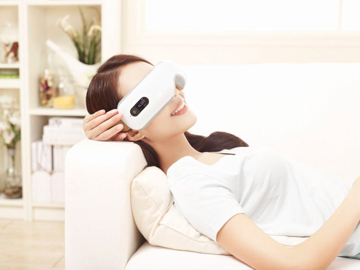 woman on sofa using eye massager 29